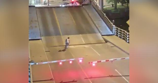 Una mujer intenta cruzar en bici un puente levadizo justo cuando se está levantando