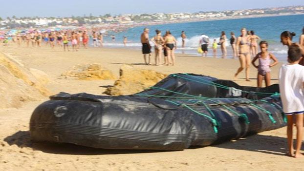 Una patera de inmigrantes desembarca en una playa abarrotada de Chiclana