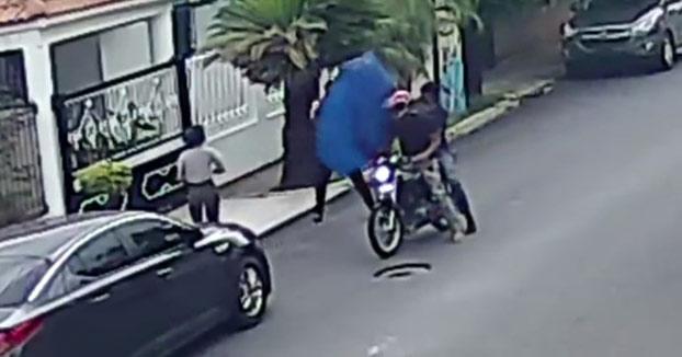 Utiliza un paraguas para evitar que unos ladrones en moto le roben