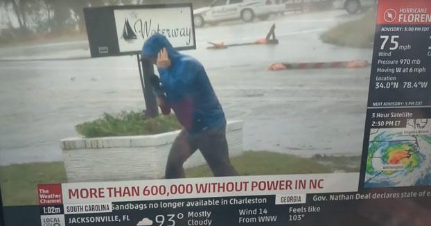 Un reportero lucha en directo contra el viento huracanado y entran en plano dos peatones tan campantes
