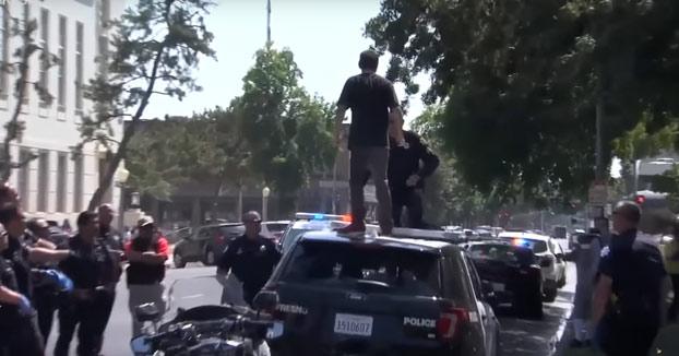 Pensó que sería divertido ponerse a saltar encima de un coche patrulla