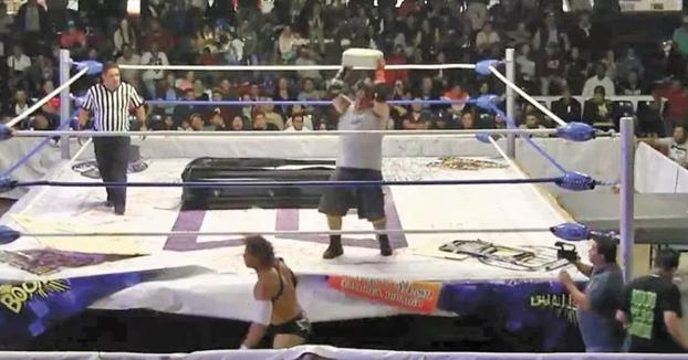 Un luchador le rompe un bloque de cemento en la cabeza a su rival durante un combate de lucha libre