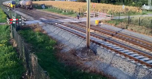 Un ciclista cruza las vías con la barrera bajada y casi es arrollado por un tren