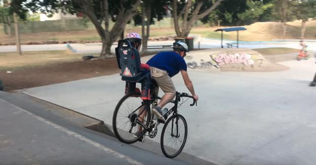 Padre bajando unas rampas del skatepark con su hijo detrás en la bicicleta