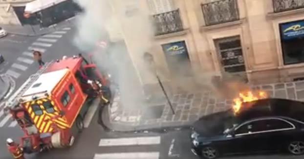 Actuación de unos bomberos para apagar un Mercedes en llamas en la calle