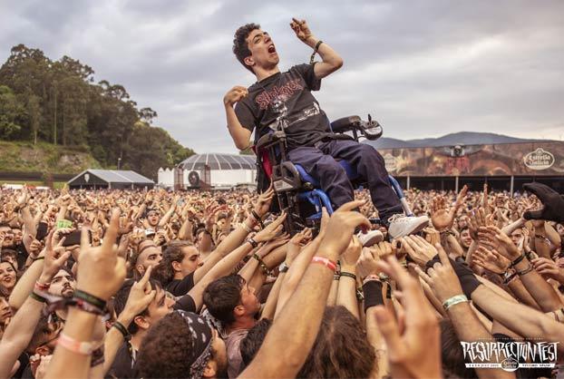 Momento en el que decenas de personas llevan en volandas a un chico en silla de ruedas en el concierto de Arch Enemy durante el Resurrection Fest