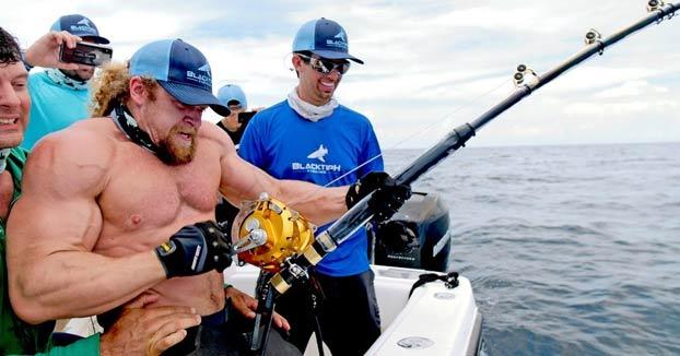 Hombres fuertes intentando pescar un mero Goliat