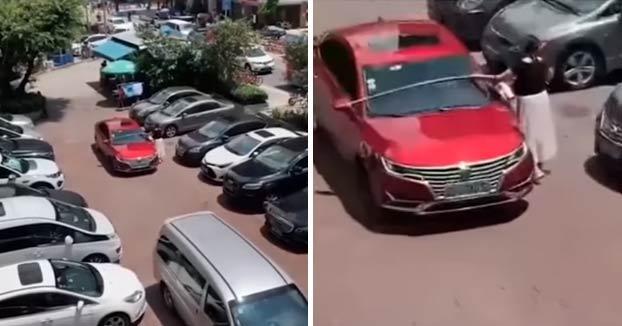 Una conductora intenta meter su coche en un hueco de un parking midiéndolo con un metro