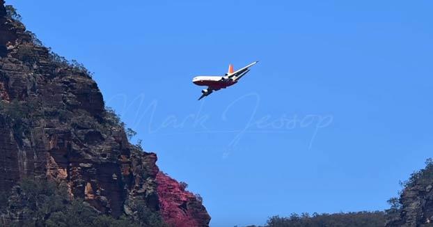Avión echando retardante de fuego sobre varios focos en un monte australiano