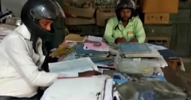 Unos empleados indios usan casco de moto en sus oficinas por miedo a que se les caiga encima el edificio