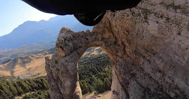 El paracaidista Alejandro Villar atraviesa un agujero de tres metros de ancho mientras hace wingsuit en el Pirineo Aragonés