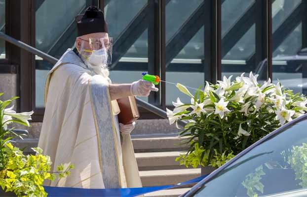 Un sacerdote de Detroit rocía agua bendita con una pistola de agua para mantener el distanciamiento social