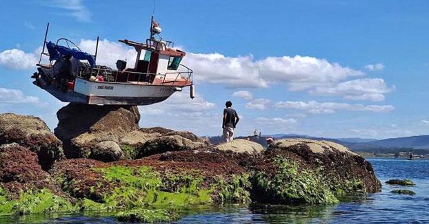 Un barco amanece suspendido sobre una roca de Punta Cabreira, en La Toja