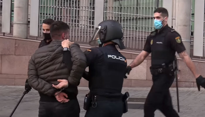 Policía dando un cabezazo con el casco a un detenido esposado e inmovilizado en Madrid