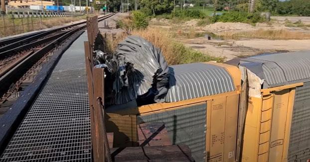 Tren pasa bajo un puente demasiado bajo y es afeitado, también los coches que transportaba