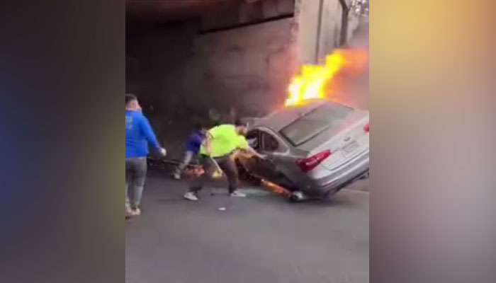 Un grupo de personas trata de rescatar a dos personas de un coche que se estrelló contra un pilar de hormigón y empezó a arder