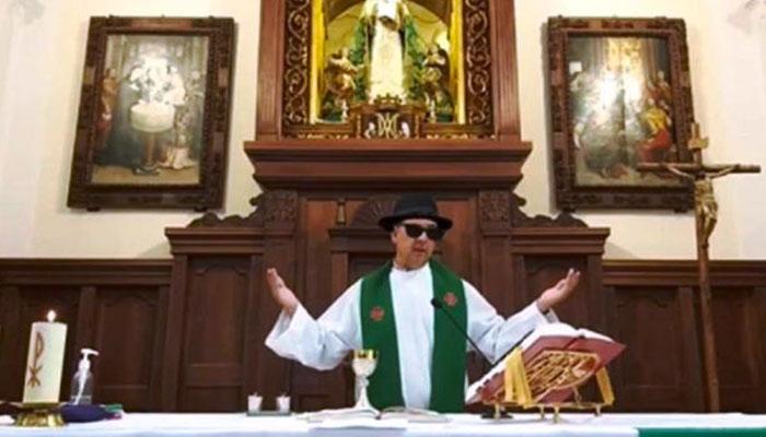 Un cura oficia misa telemática con sombrero y gafas de sol por error