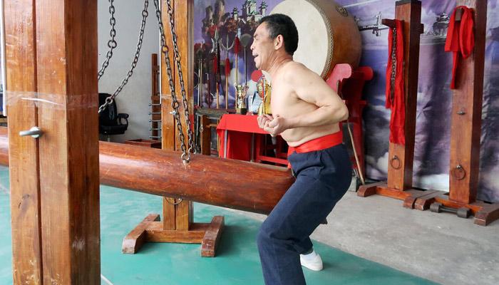El pequeño grupo de maestros de artes marciales que practica el 'iron crotch', recibir un golpe en la entrepierna con un tronco de 40 kilos