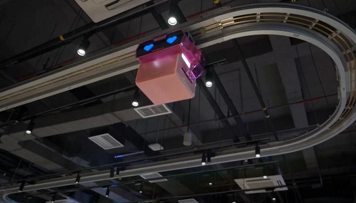 Robots sirven comida desde el techo en un restaurante de China
