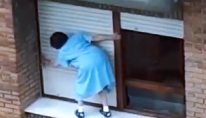 Una mujer de Gijón limpiando las persianas de su casa por fuera en un séptimo piso