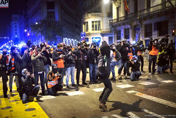 Los medios sacan fotos mientras un hombre arroja una botella contra una comisaría