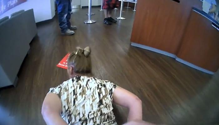 Una mujer que se negó a usar mascarilla dentro de un banco es esposada por un policía y detenida