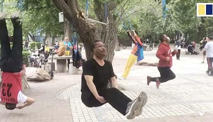 Unos jubilados chinos promocionan el colgarse del cuello como remedio para los dolores de espalda y cuello