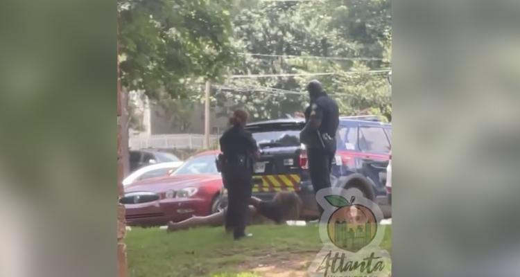 Un policía le propina una patada en la cara a una mujer esposada y tumbada boca abajo